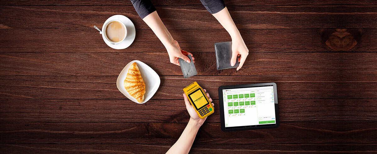 Mão entrega Moderninha Pro para outra mão que entrega cartão ao lado de tablet sobre mesa