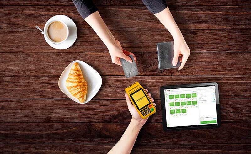 Mão segurando Moderninha Pro ao lado de tablet com app e outra mão entregando cartão
