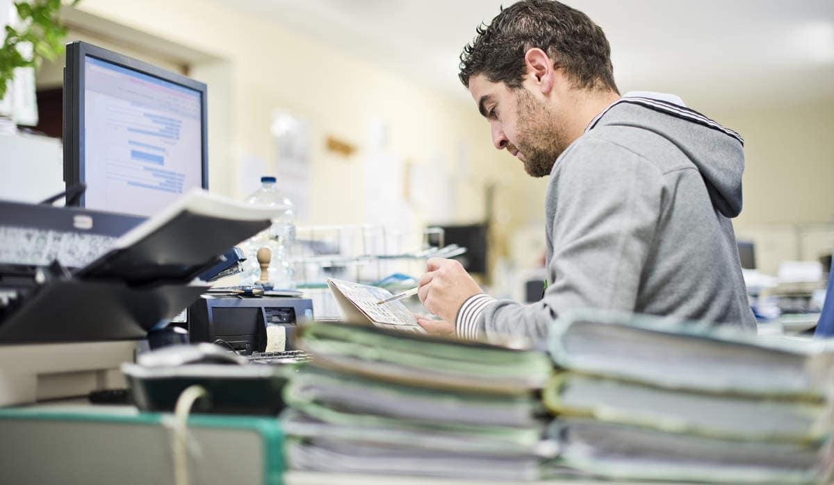 Homem em frente a computador com diversos papéis e pastas em volta