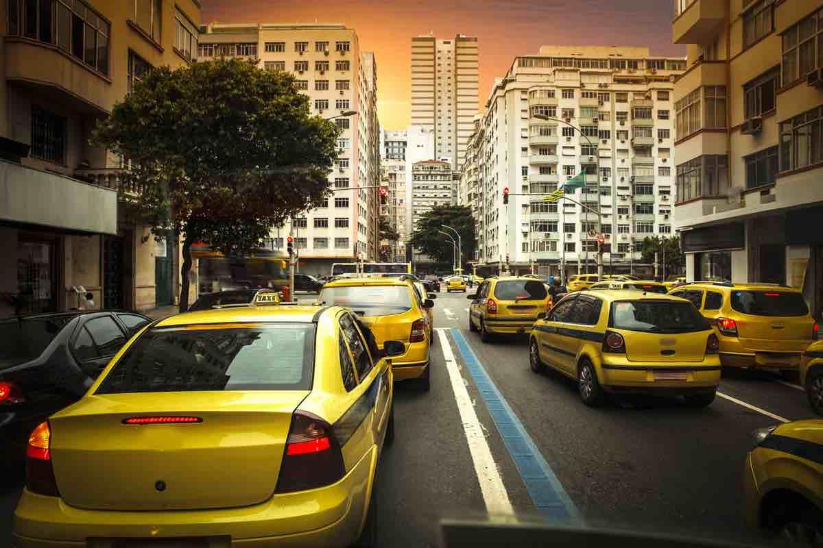 Fila de táxis engarrafados em rua de mão dupla de cidade grande