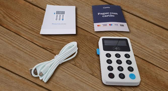 Maquinão iZettle sobre mesa ao lado de cabo USB, manual de instruções e adesivos de bandeiras
