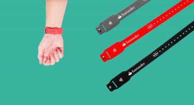 Braço com a pulseira Santander Pass e três pulseiras em diferentes cores ao lado