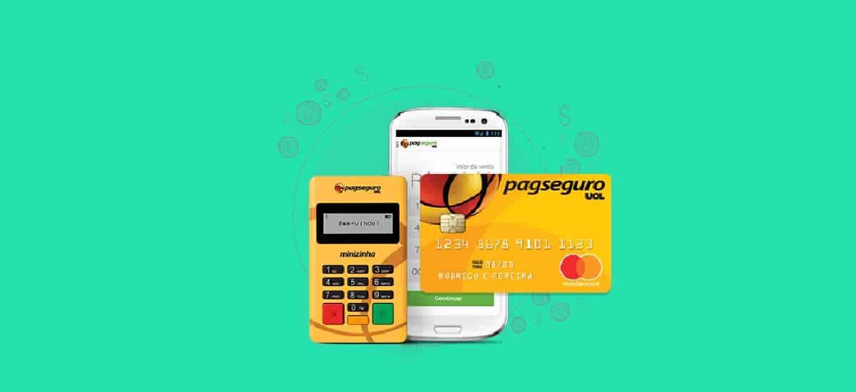 Foto da Minizinha com o cartão pré-pago da PagSeguro e um celular, com fundo marrom