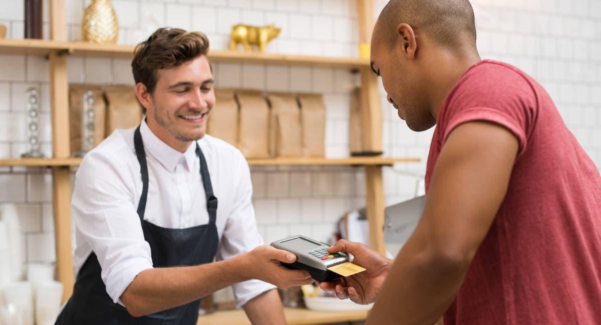 Cliente digitando senha em máquina de cartão enquanto vendedor de padaria aguarda
