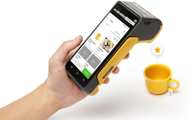 Mão segurando Moderninha Smart ao lado de xícara de café