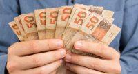 Maos segurando leque de notas de dinheiro
