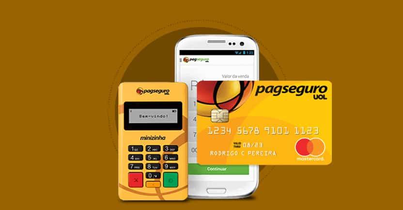 Maquininha de cartão Minizinha ao lado de cartão pré-pago PagSeguro e celular dobre fundo marrom