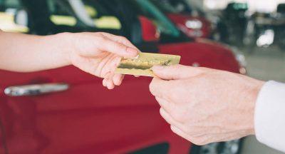Mão feminina entregando cartão de crédito para mão masculina com carro vermelho ao fundo