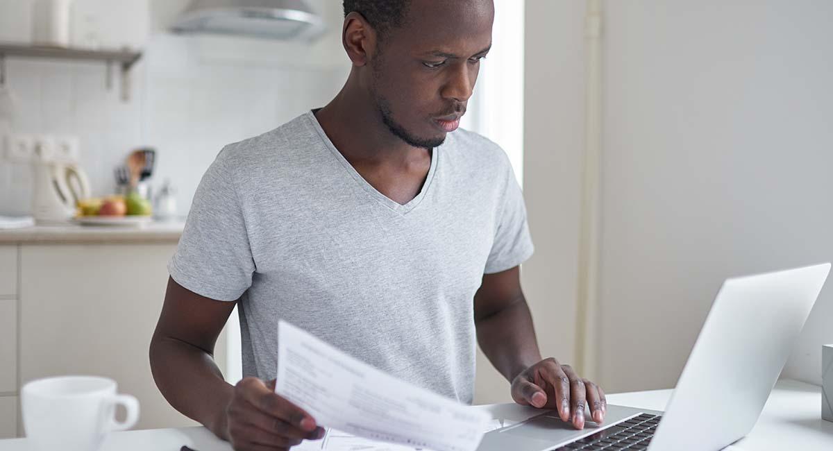 Homem sentado em frente a computador pagando contas pela internet