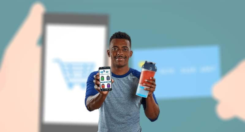 Homem segurando celular que mostra a Loja Virtual Uol e copo de suplemento na outra mão
