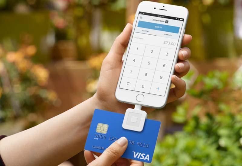 Ilustração mostrando uma mão segurando um celular acoplado ao Square Reader e um cartão