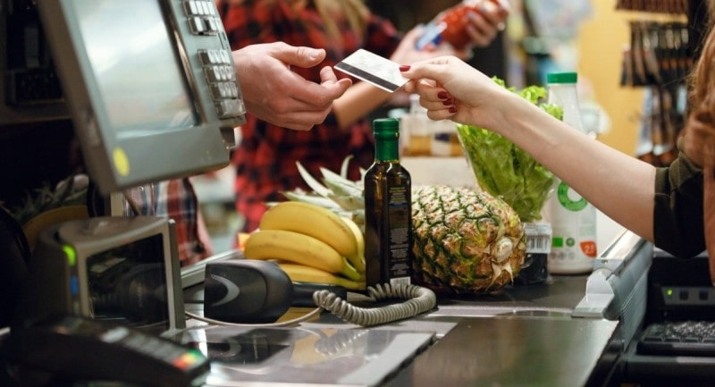 Foto ilustrando mulher fornecendo cartão em supermercado e o sistema PDV do mesmo