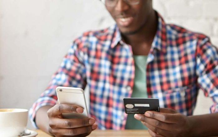 Homem digitando dados de cartão no celular
