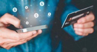 Homem usando smartphone em uma mão e segurando cartão de crédito na outra
