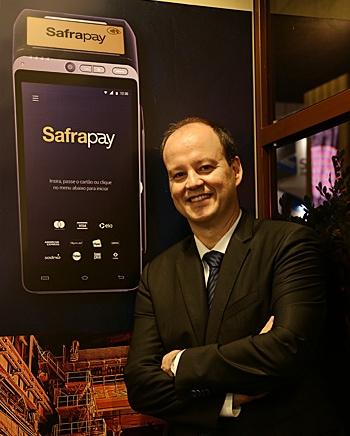Ilustração do superintendente do Banco Safra Gustavo Gomes ao lado de uma foto de uma maquininha SafraPay