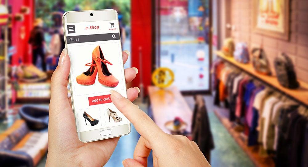 Ilustração de uma pessoa realizando compra em loja virtual pelo celular, com fundo de uma loja física