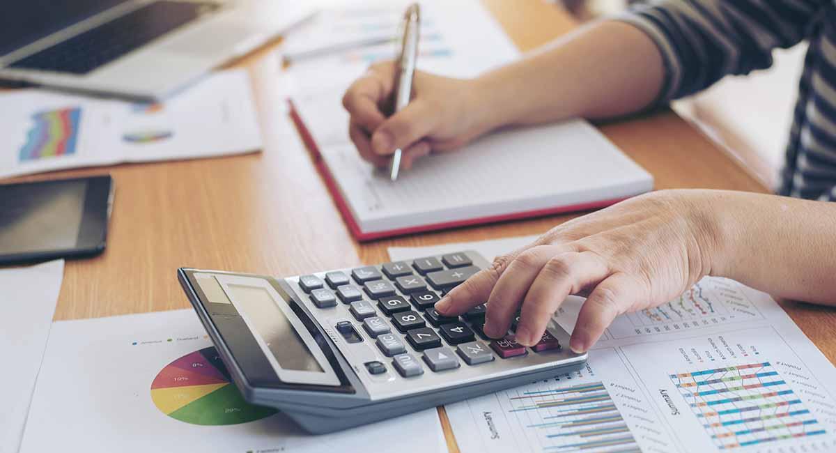 mãos calculando impostos com calculadora sobre mesa com papéis
