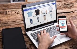 Homem vendo loja virtual no laptop e pagando pelo celular
