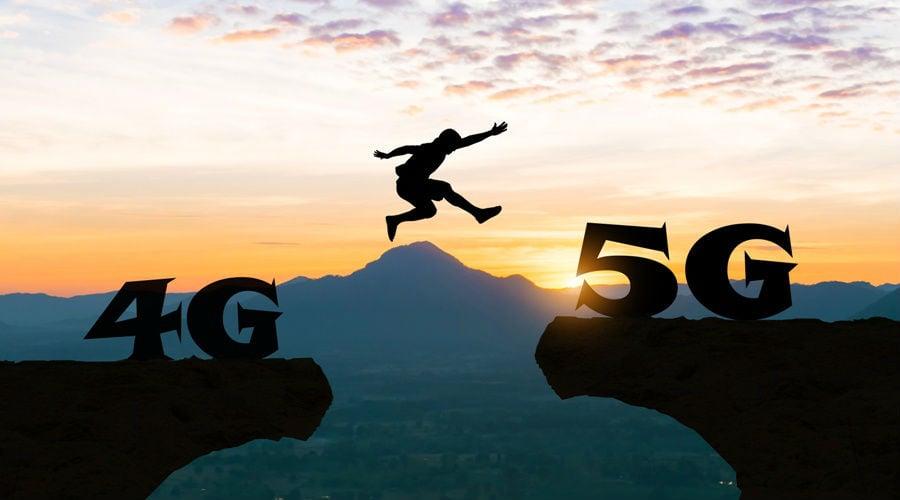 Pessoa saltando de uma montanha com escultura escrita 4G para outra com 5G