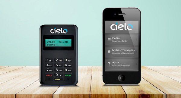 Cielo Mobile ao lado de um smartphone sobre mesa em fundo azul