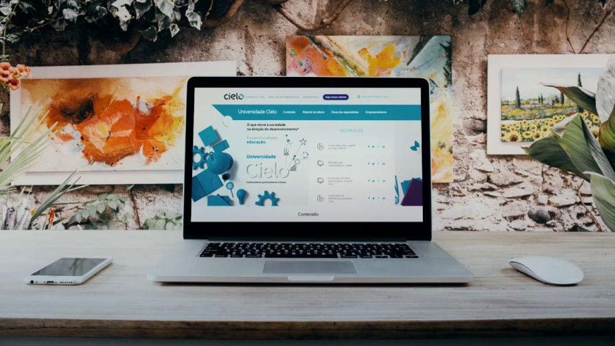 Ilustração de um celular em cima da mesa ao lado de um desktop com tela mostrando a página da Cielo Universidade