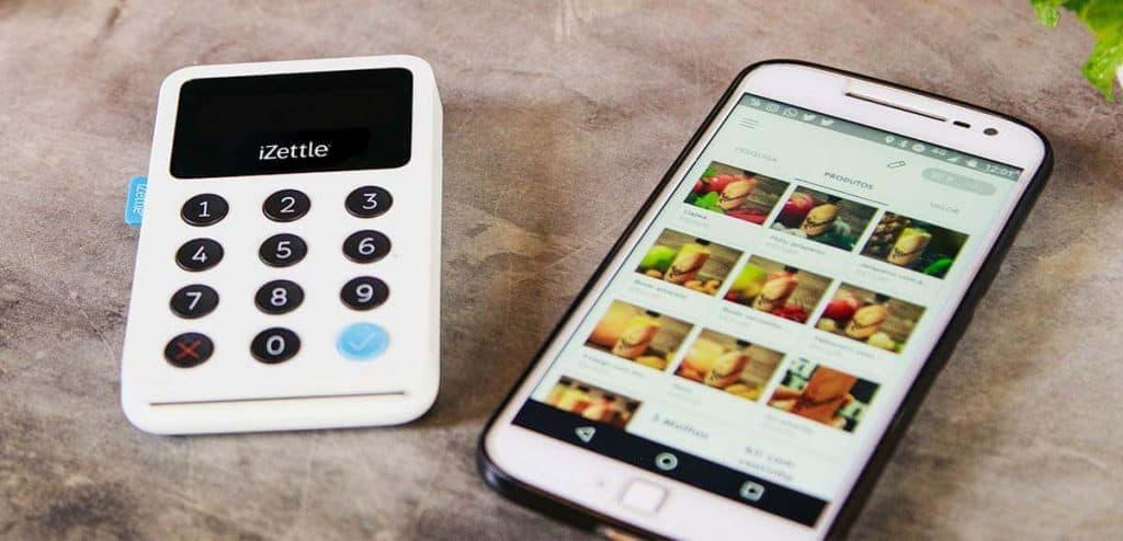 Maquinão iZettle ao lado de celular mostrando galeria de fotos
