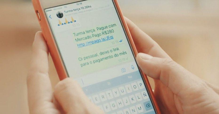 Mão segurando um smartphone com a tela mostrando um link de pagamento do Mercado Pago enviado por rede social