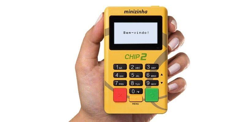 Minizinha Chip 2 sendo segurada por uma mão em zoom