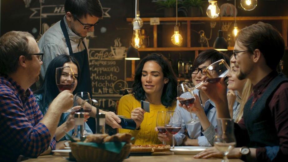 Garçom levando máquina de cartão até uma mesa de amigos em um restaurante