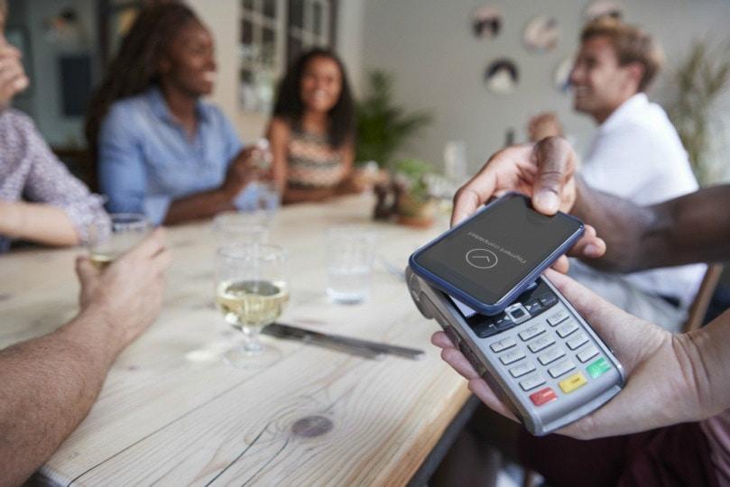 Ilustração mostrando pagamento sem contato com entre celular e máquina de cartão, com pessoas sentadas em uma mesa