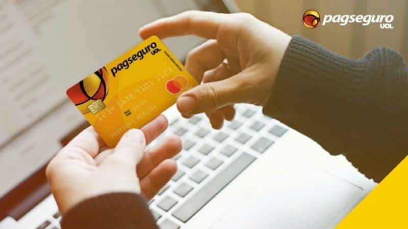 Ilustração de uma pessoa segurando cartão pré-pago PagSeguro com um computador de fundo