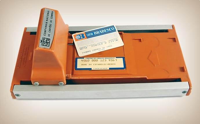 Ilustração do primeiro leitor de cartão manual comercializado no Brasil e do primeiro cartão de crédito brasileiro