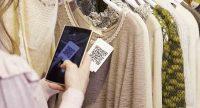 Mulher escaneando um QR Code com seu celular de uma etiqueta em uma blusa