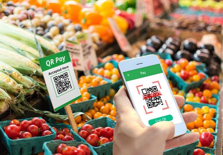 Pessoa escaneando com celular o QR Code de tomates em uma bancada de legumes