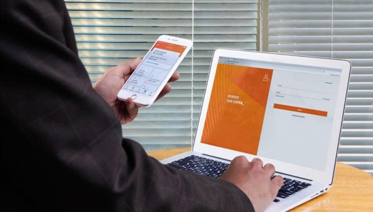 Homem segurando celular com o app Rede na tela e mexendo em um desktop com a outra mão