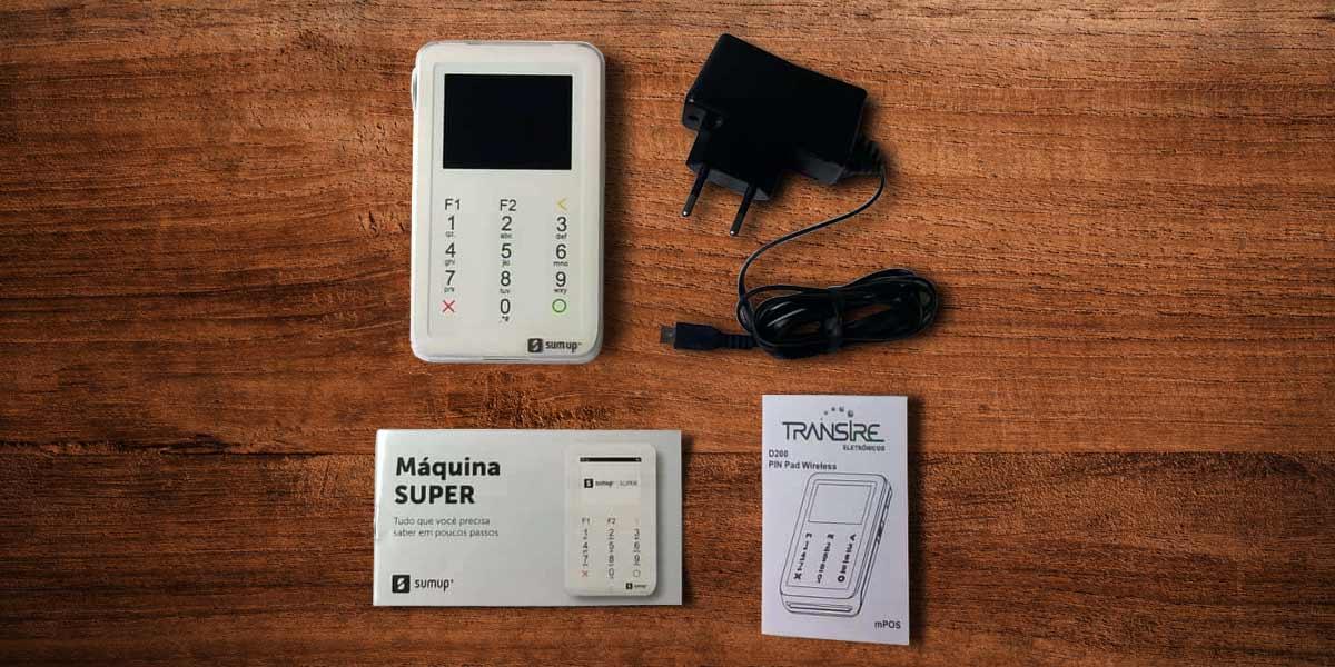 Itens encontrados na caixa da SumUp Super: máquina, manuais e cabo USB em cima de uma mesa