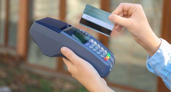 Mulher usando cartão de tarja magnética em uma maquininha de cartão