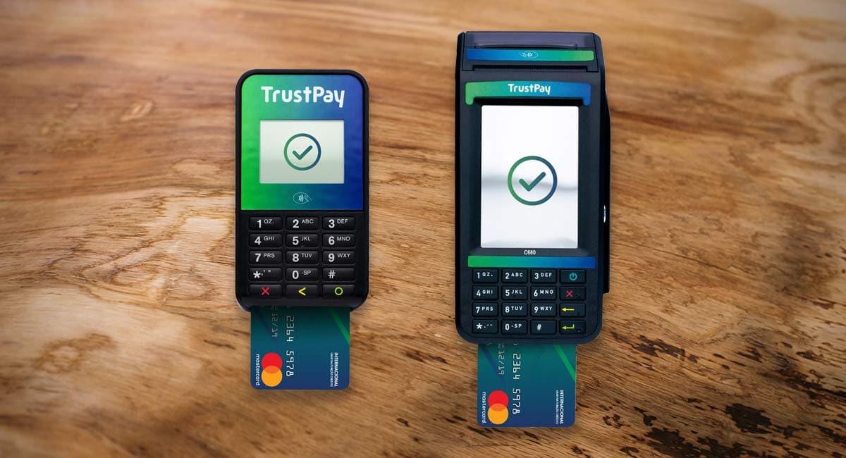 Trustpay Slim e Ultra em fundo amadeirado com cartões Mastercard