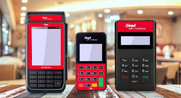 Máquinas de cartão iFood Ultra, Pocket e Fast sobre uma mesa de madeira e fundo de loja
