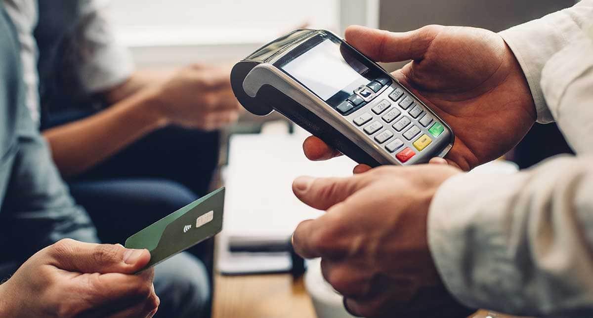 mão entregando cartão de crédito para oura maão segurando máquina de cartão