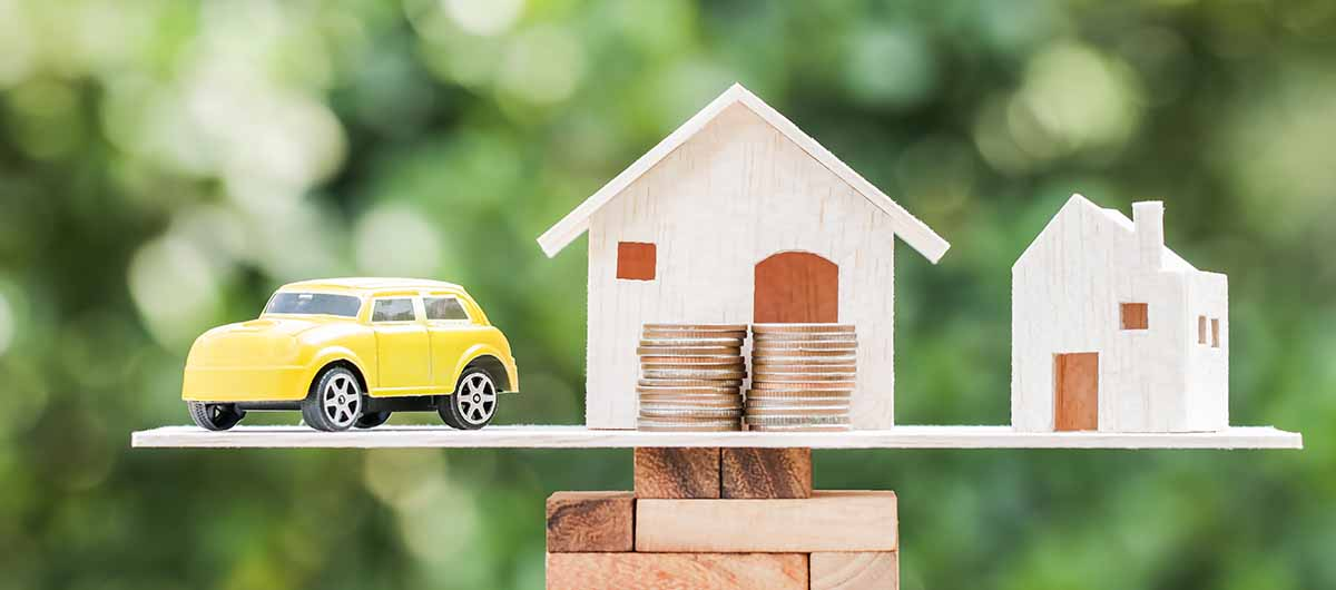 Miniatura de carro e casa ao lado de moedas representando garantia de imóvel