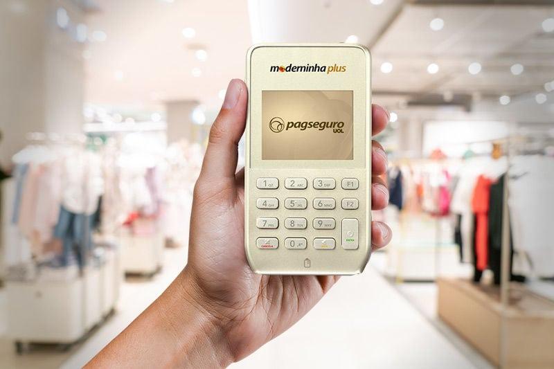 Mão segurando a Moderninha Plus com fundo de uma loja