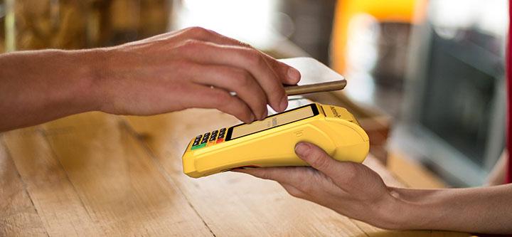 Mão segurando celular para fazer pagamento com a Moderninha Pro