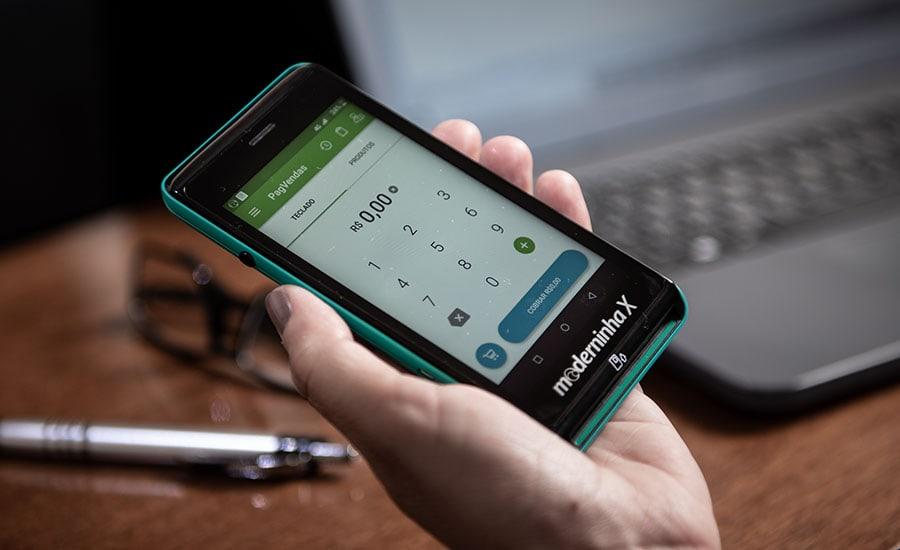 Maquininha Moderninha X recebendo pagamento com laptop e caneta ao fundo