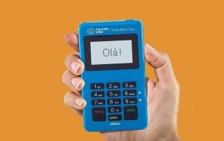 Mão segurando maquininha Mercado Pago Point Mini chip sob fundo laranja