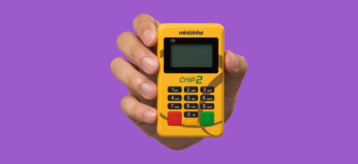 Mão segurando a maquininha Minizinha Chip 2