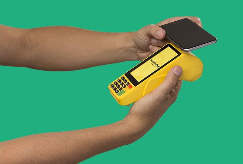 Mão com celular e outra mão com Moderninha Pro 2 aceitando pagamento com NFC