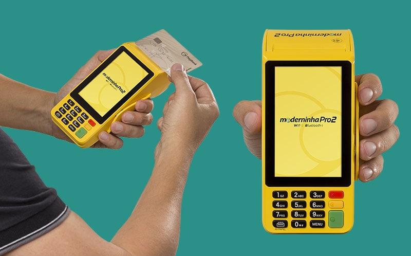 Maquininha Moderninha Pro 2 de frente e na mão aceitando cartão