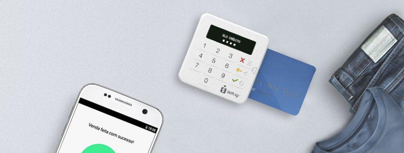 SumUp Top com cartão inserido, ao lado de um celular e uma calça