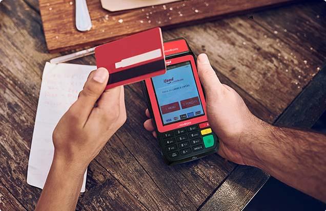 Mão pagando com cartão na maquininha iFood Ultra